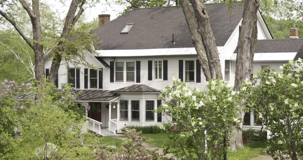 white house with black roof and black shutters surrounded by green lawn and spring blossoming lilacs and trees