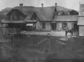 historic black and white photograph of two tone house with porch and awnings with a horse and lantern post out front