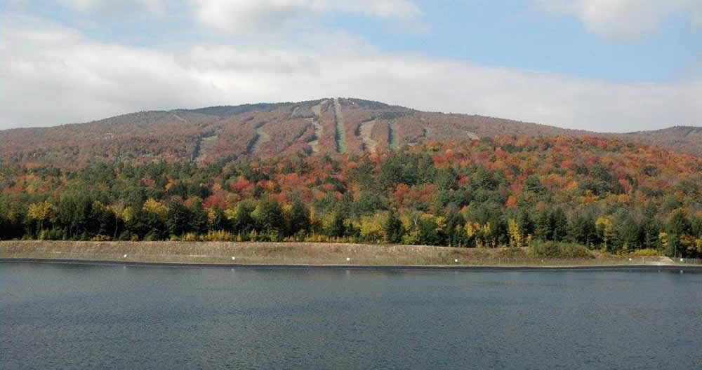 autumn colors of reds and greens on a ski mountain behind a calm lake.