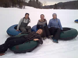 four teen girls sitting on green and blue inner tubes on a tree lined very snowy meadow