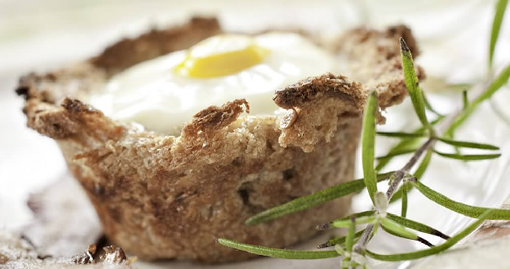 cup made of golden brown bread with white baked egg and yellow yolk center garnished with green rosemary sprig, all on white plate with bacon out of focus in foreground