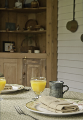 simple table setting of a plate with light brown folded napkin with fork and small pottery mug and clear glass filled with orange juice on green country tablecloth with wooden shelves and white porch clapboards in background