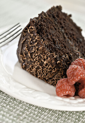 one piece of dark brown chocolate cake with chocolate frosting and shavings laying on its side bright red raspberries all on contrasting white plate with pale green table linen