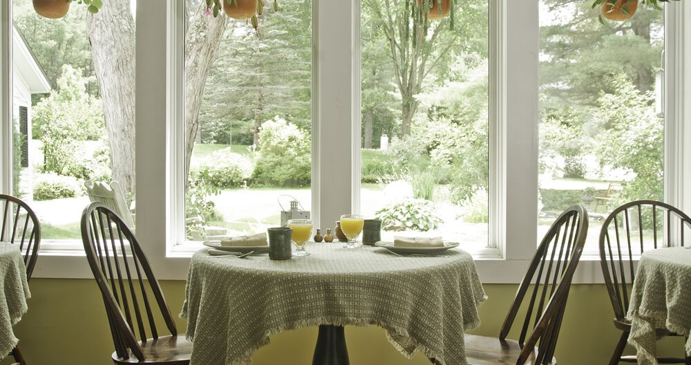 ight green tablecloth on table set for breakfast in front of sunny, greenery filled windows