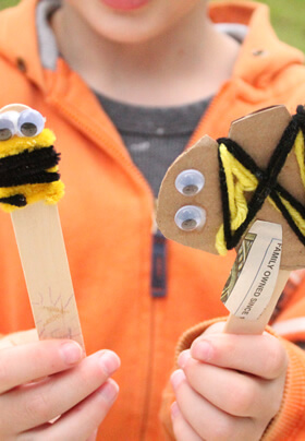close up of young hands holding two different child crafts, both with googly eyes and yellow and black yarn or pipe cleaners fastened to resemble a honeybee