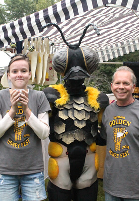 colorful and busy backdrop of vendor tents and signs but in the center of it is two volunteers wearing matching gray and yellow Honey Festival t-shirts standing on either side of a person fully costumed as a honeybee with honeycombed shaped platelets on her belly and a large head with two giant eyes and antennae