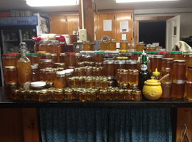 Maybe 100 jars of honey of various sizes and shapes all stacked on top of one another sitting on top of a black stone kitchen counter with country wooden cabinets in the background