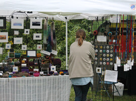 a table full of colorful and varied craft bowls, jewelry, with small framed art hanging on wire screen behind table with one person browsing the merchandise