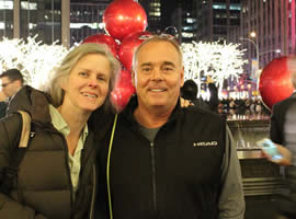 man and woman wearing winter coats posing in front of Christmas decorations with city buildings behind them