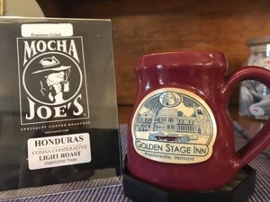 red pottery mugh sitting on table next to table top sign announcing Mocha joe's coffee