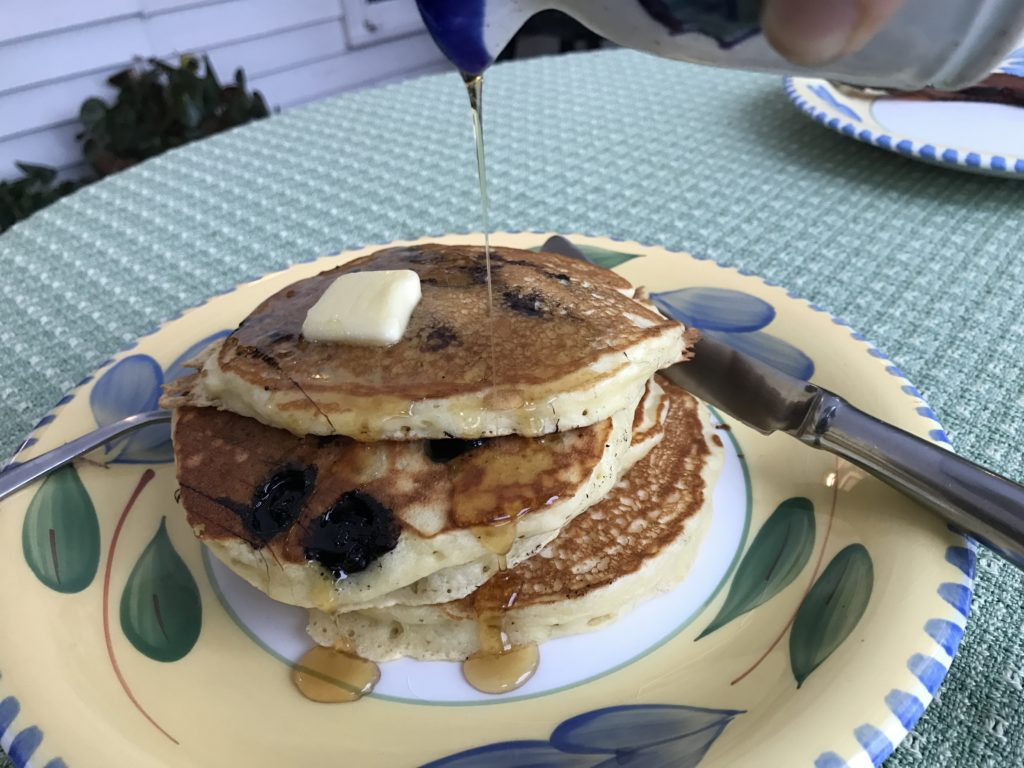 dinner plate with three blueberry pancakes with a pat of butter on top and syrup being poured onto the stack
