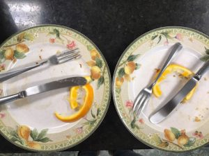 two plates, each with knife and fork and empty orange rind and leftover pancake crumbs