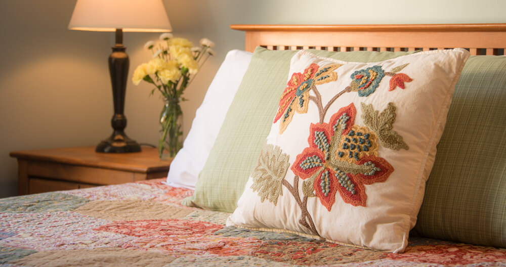 embroidered floral pillow rests against other bed pillows on top of quilted bed with lamp and flowers on end table in background