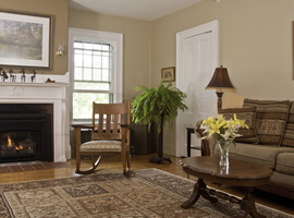 living room with fireplace, rocking chair, bushy fern, couch with table and patterned area rug on hardwood floor