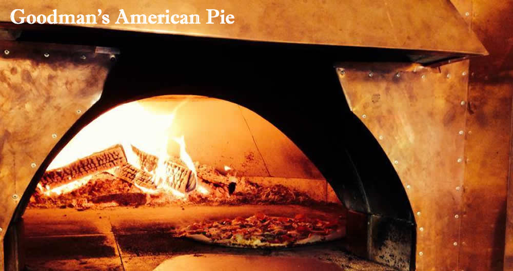 looking into a copper encased wood fired pizza oven, the pizza paddle rests on black flour-covered polished stone in front while deep inside is a pizza baking next to burning logs. The colors are warm and golden.