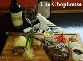 wooden cutting board with large cooked steak and decoratively placed garnishes such shredded orange and red vegetable, mashed potatoes, three white mugs of sauces, a popover, and in the background a bottle of wed wine, with an empty wine glass, and four white-with-gray-stripes linen napkins each rolled individually