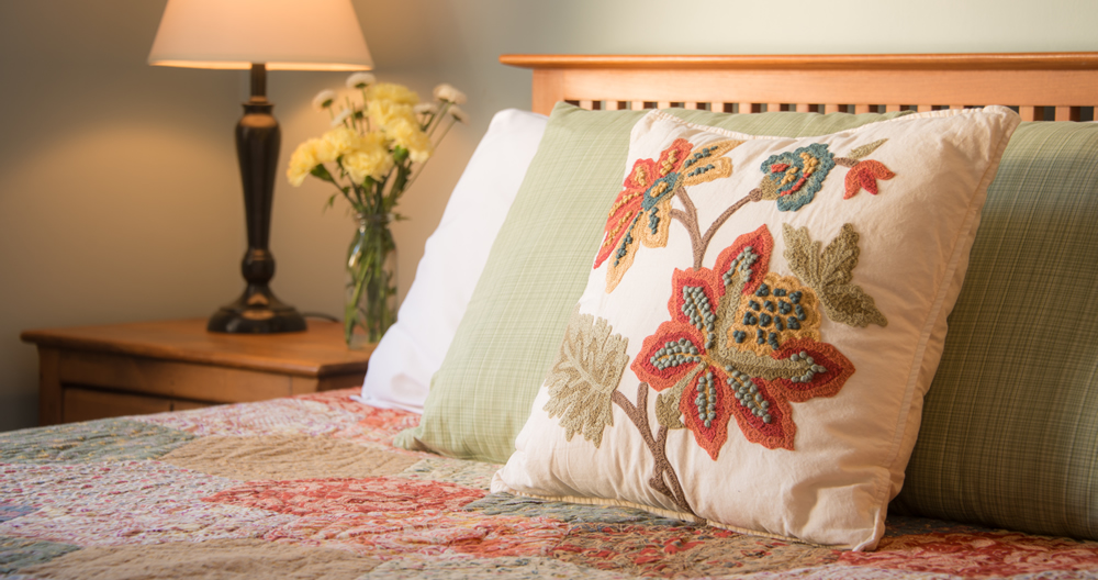 burgundy and gold floral embroideryy on cream colored pillow resting on quilted bed with lamp and vase of flowers in background