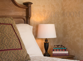 lamp and stack of books with brown reading glasses on a nightstand next to a bed with brown and burgundy pillows and golden brown headboard