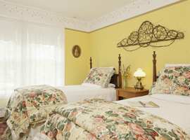two twin beds side by side with white bedspread and floral comforters at the foot in a bright yellow room with two white-curtained windows