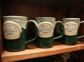 Three green pottery mugs lined up on wooden shelf, each emblazoned with a sketched image of the inn and the name Golden Stage Inn