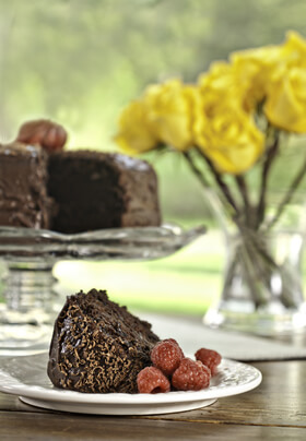 small plate with chocolate cake with red raspberries in front of full cake display and vase of yellow roses
