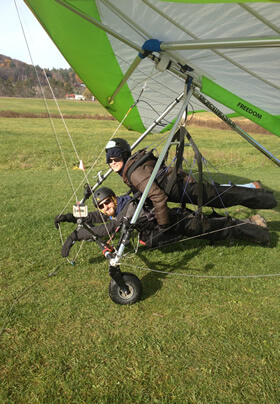 two adults hanging in harnesses under large hang gliding kite frame wearing helmets preparing for flight