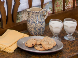 speckled gray and blue pottery pitcher with two glasses of milk and a pewter tray of cookies on an antique wooden trunk