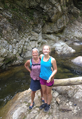 mother and teenage daughter in hiking clothes, looking up at camera, standing on rocky ledge with rocky river set low behind them and a wall of rough rock with woods above them
