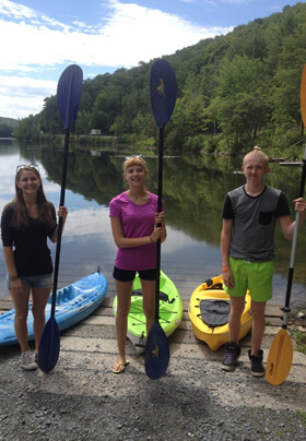three young adults standing in a row, each with an upright paddle and each with bright blue, green, or yellow kayak behind them, and a tree lined lake with blue sky in the background