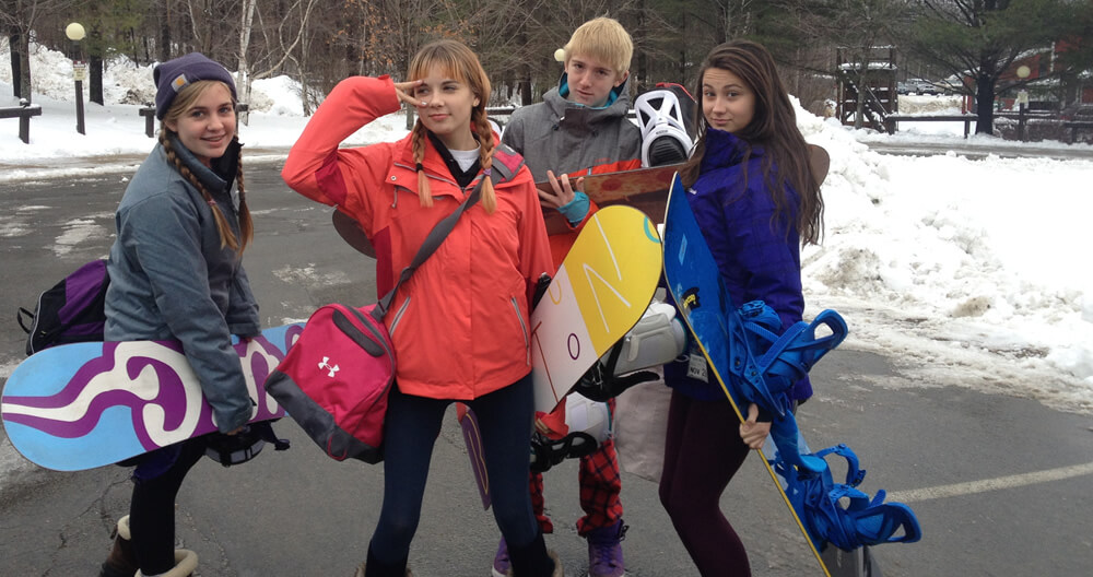 four teenagers with colorful winter coats and boots standing in parking lot with snowboards and gear posing silly for camera