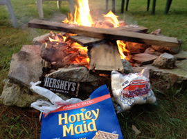 old boards burning in a stone circle campfire with a wrapped hershey's chocolate bar, a bag full of white marshmallows, and an opened blue box of graham crackers in the foreground
